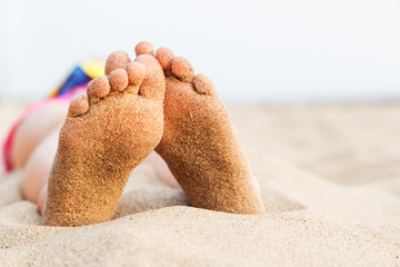 Feet girl relaxing on the beach after swimming