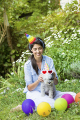 happy young woman celebrating birthday with her dog ,balloons and hats in a summer garden