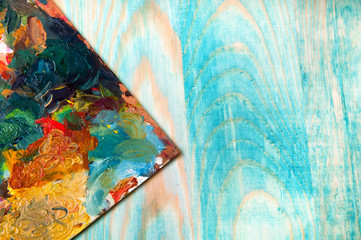 Painting palette on colored wooden background