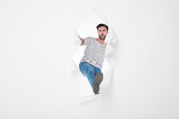 casual man breaking the paper background