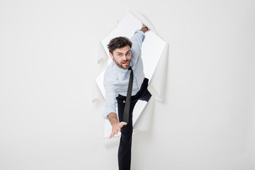 office man with elegant outfit and tie breaking the paper backgr