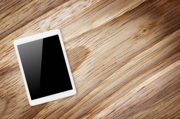 Digital tablet on wooden background.