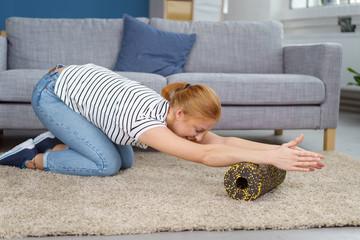 frau macht zuhause übungen mit einer blackroll