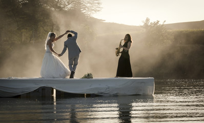 Bride and Groom dancing on a lake to music.