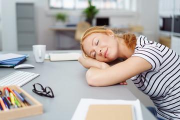 frau schläft am schreibtisch im büro