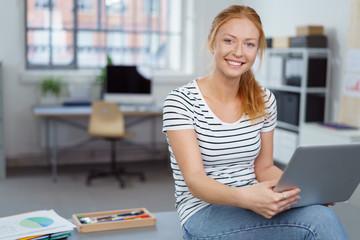 junge frau mit sommersprossen arbeitet in einem modernen büro
