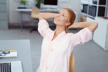 lächelnde frau im büro lehnt sich entspannt zurück