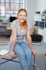 zufriedene auszubildende sitzt auf dem schreibtisch im büro