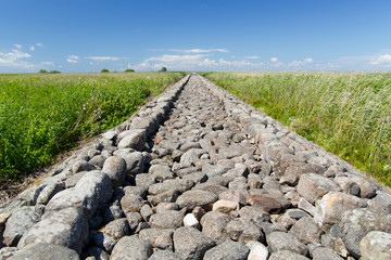 Stone pathway to the Baltic sea and green field at summer.