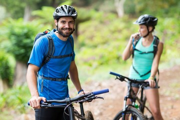 Man standing with mountain bike in forest