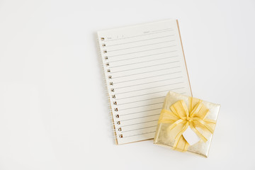 Top view of small notebook with gold gift box on white backgroun