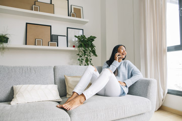 Laughing young woman sitting on couch at home telephoning with cell phone