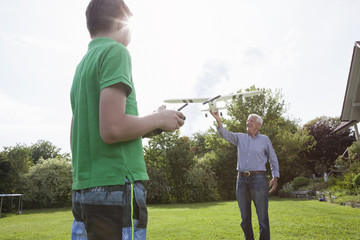 Grandfather and grandson with model airplane in garden