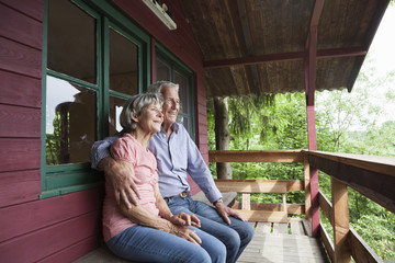 Happy senior couple relaxing on porch of log cabin