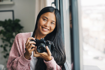 Portrait of smiling young woman with camera looking near window