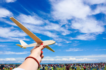 Girl holding toy plane at an airshow with crowd in the backgroun
