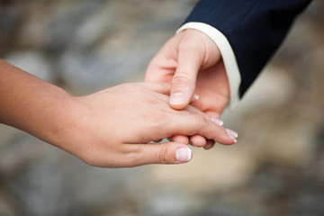 Young married couple holding hands, close-up. Marriage concept