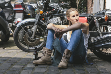 Young woman with beer bottle sitting next to motorbike