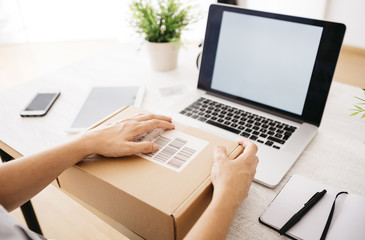 Woman unpacking parcel on her desk