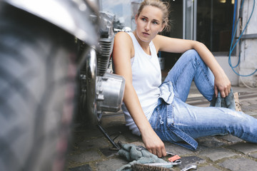 Young woman sitting next to motorbike