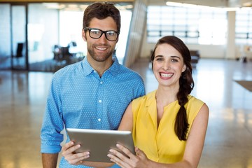 Business executive and co-worker holding digital tablet
