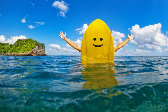 Young happy surfer girl sit on yellow surf board with smiley face and have fun. Healthy lifestyle, people water sport lessons, swimming activity in summer surf camp on family beach vacation with child