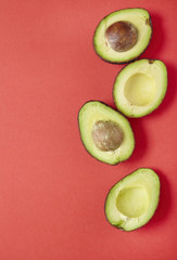 Avocado halves arranged on a red background forming a page border