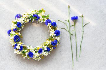 Bluet floral wreath on concrete background.