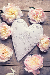 Tender pink peonies flowers  and decorative heart on  vintage  w