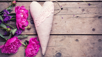 Pink peonies flowers and decorative heart on aged wooden backgro