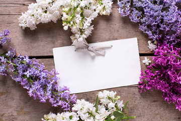 Aromatic lilac flowers  and empty tag on vintage wooden table.