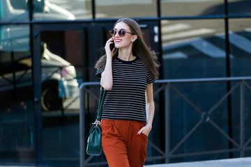 Beautiful young woman talking on mobile phone in the street.