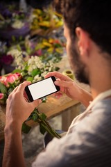 Male florist taking photograph of flower bouquet