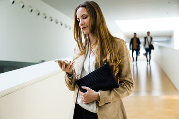Beautiful young businesswoman using her mobile phone.