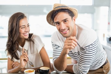 Smiling couple having dessert