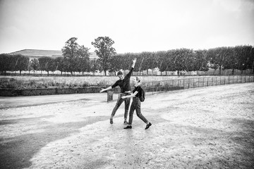 Happy Man and woman dancing on Paris street during hard rain. Black and white photography. Summer time.