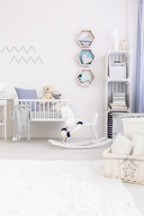 Very bright and natural baby room with white fluffy carpet, a rocking horse and a cradle