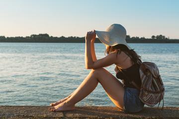 Hippie girl enjoying Sun on a lake