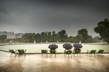 People seating by pond in Jardin Tuileries, saving from hard rain under umbrellas. Paris.