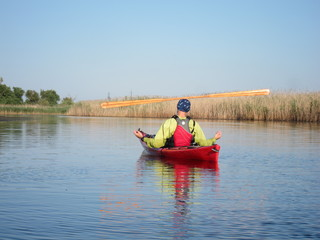 Greenland wooden paddle on the head of man in red kayak in summer on river. Zen Meditation