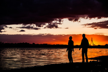 Happy man and woman couple walking and holding hands on a beach with bright colorful sunrise on the background, romantic couple in love walking at sunset, woman and man in love walking hand in hand