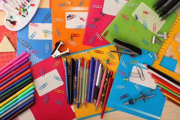 Background of school notebooks, pencils, pens, staplers, triangle and other school supplies