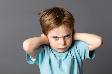 stubborn kid with an attitude ignoring parents scolding, blocking ears