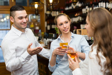 Two girls with man at bar