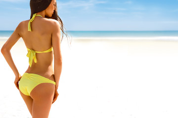 Beautiful woman in bikini standing with her arms raised to her hips enjoying looking view of ocean on hot summer day