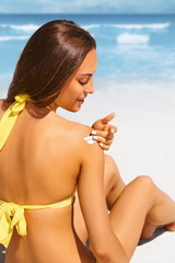 Young woman with sun cream on the shoulder relaxing on the beach