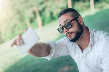 Young man at the park taking selfie