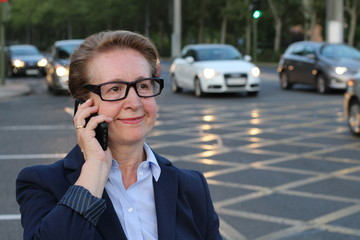 Business woman in the city making a phone call with smartphone