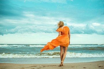 A young slender woman in orange dress is walking barefoot towards the storming sea. The train of her dress is waving. Cool wind in her hair. Outdoor shot. Copy-space.