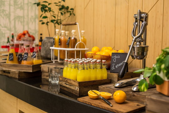 Brunch buffet with fresh orange juice in the bottles. An orange cut on a wooden chopping board and an orange juicer press